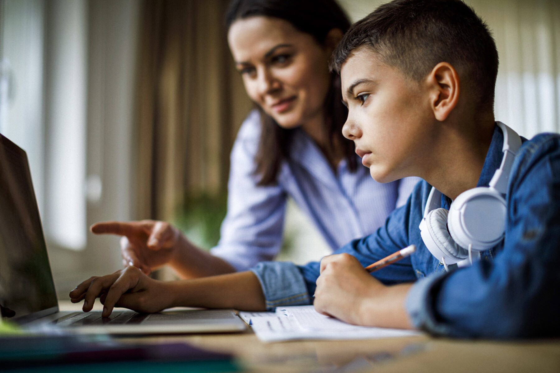 Mother helping teenager with homework