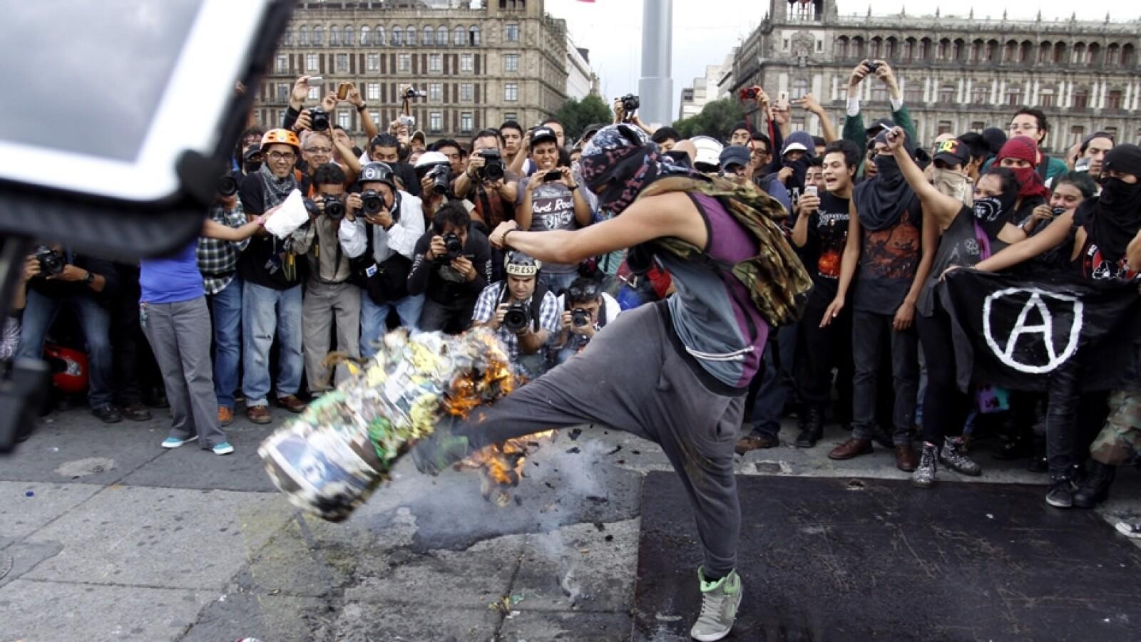 Un manifestante patea un objeto ante la mirada de sus compañeros de marcha