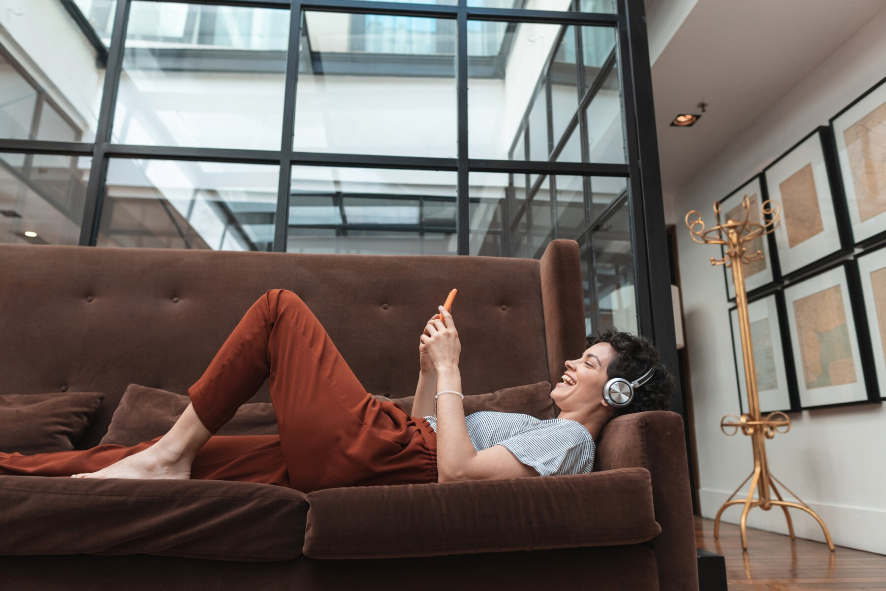 Woman lying on the couch listening to music on mp3 player