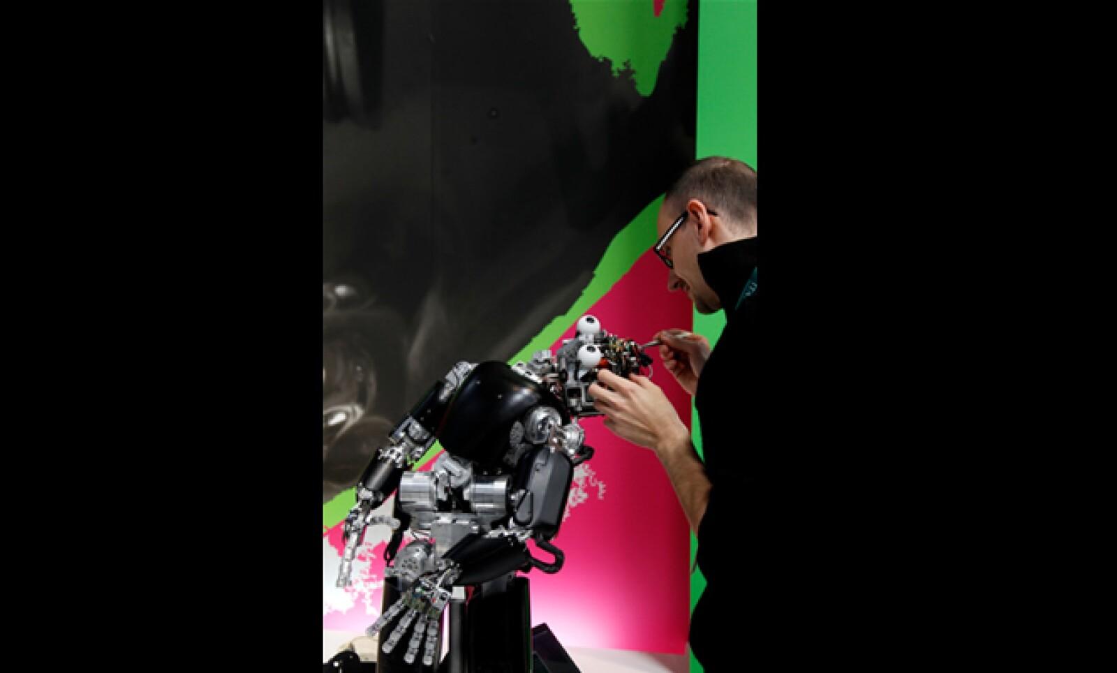 Un técnico limpia a su robot justo antes de su presentación en la feria.