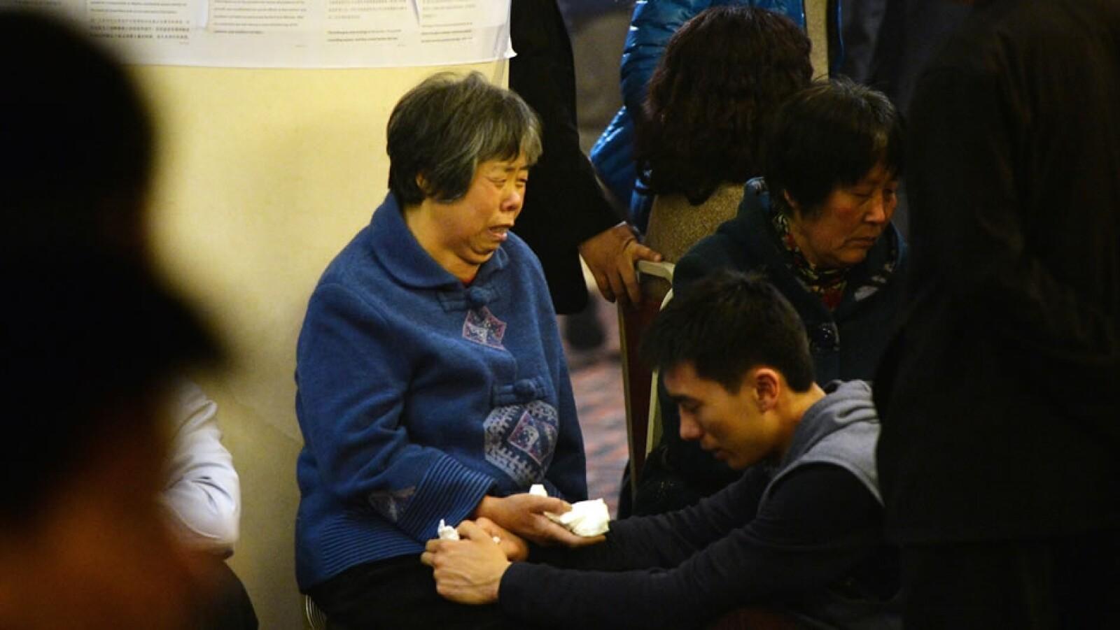 Los familiares de las personas que viajaban en el vuelo 370 de Malaysia Airlines reaccionan tras el anuncio que encontraron la aeronave este lunes