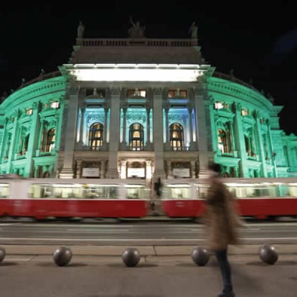 Dos peatones pasan por el Burgtheater (el teatro nacional de Austria) que se ilumina en verde por la celebración.