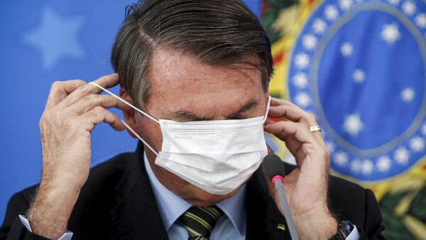 Brazil's Jair Bolsonaro adjusts his protective face mask during a news conference to announce measures to curb the spread of the coronavirus disease (COVID-19) in Brasilia