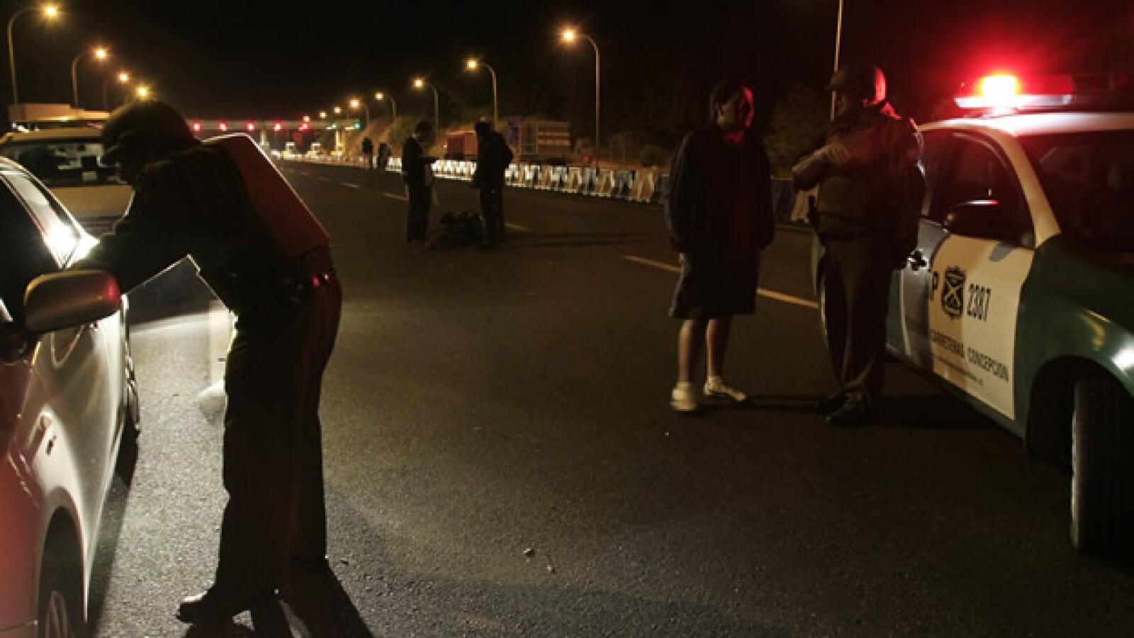 Policías chilenos inspeccionan vehículos que entran y salen de Concepción. El gobierno incrementó la seguridad por los reportes de saqueos