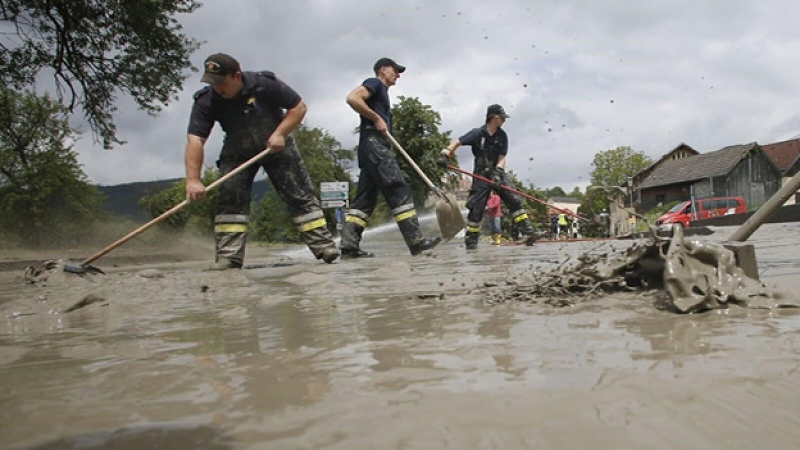 miembros del servicios de emergencias limpian las calles de una ciudad austriaca