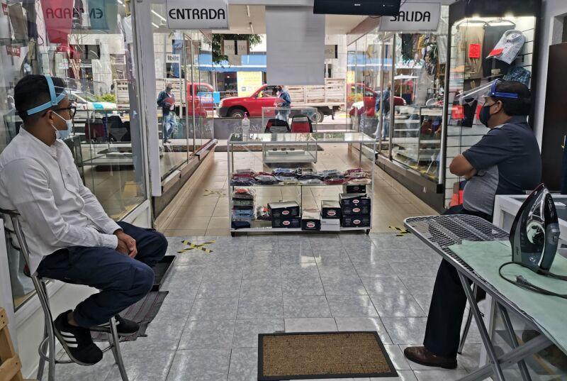 Dos vendedores de una tienda de ropa esperan la primera venta del día, en un comercio del Centro Histórico.