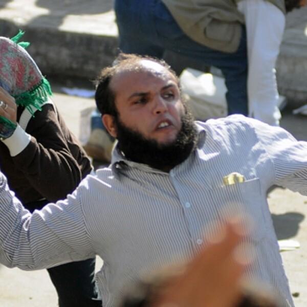 un manifestante laza una piedra