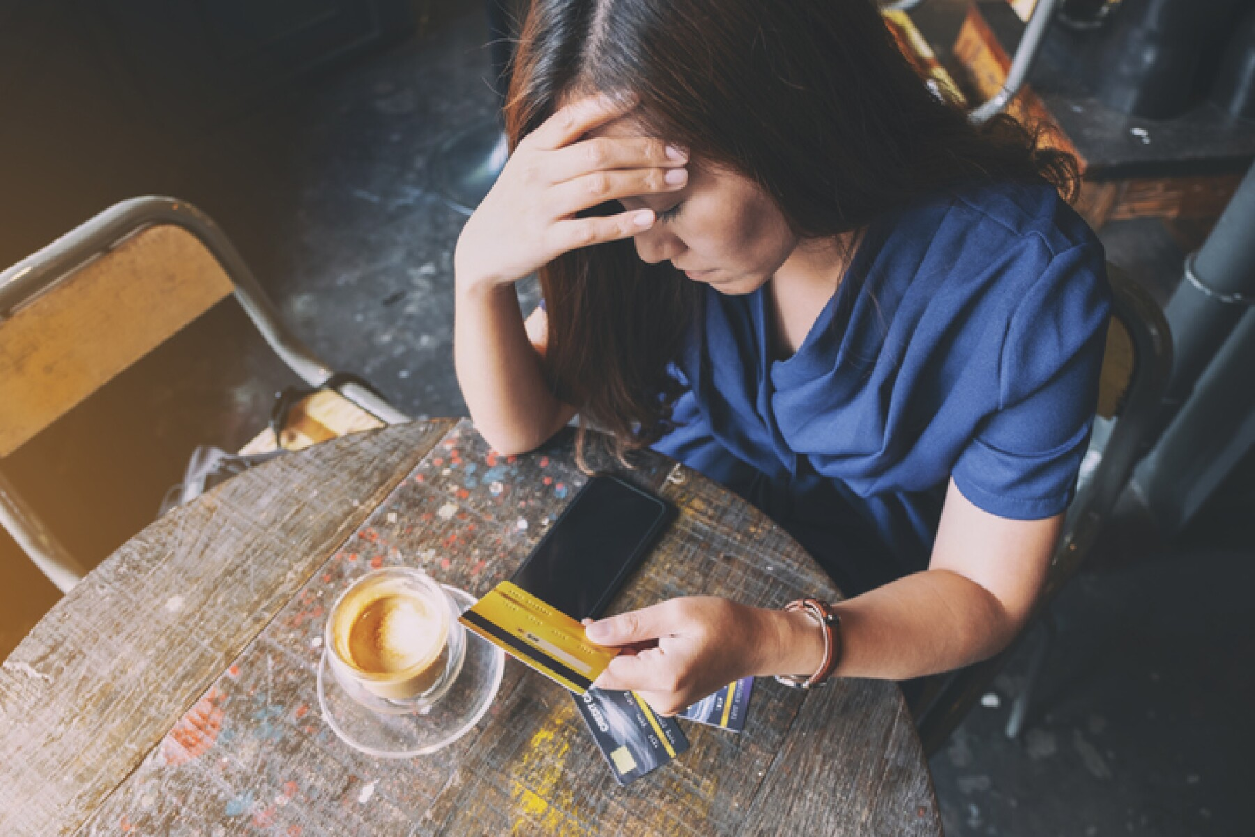woman get stressed and broke while holding credit card
