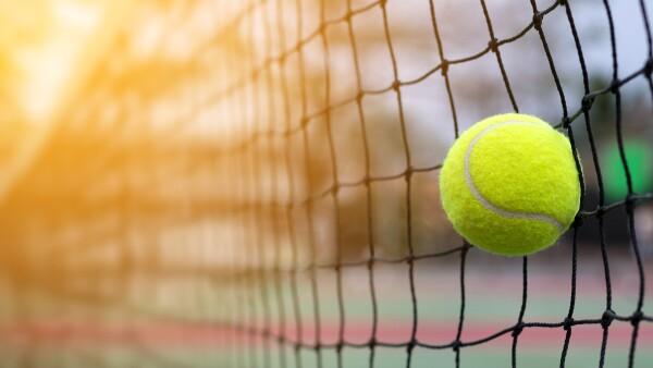 Tennis ball hitting to net on blur court background