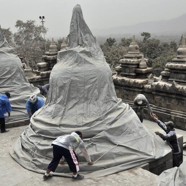 trabajadores cubren de las cenizas el templo de borobudur