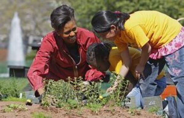 Michelle colocó con cuidado las plantas en los huecos que cavaron dos niñas, que luego regaron.