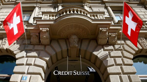 FILE PHOTO: Switzerland's national flags fly beside the logo of Swiss bank Credit Suisse in Zurich