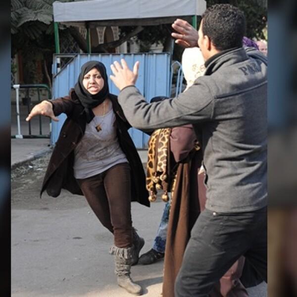 Una chica trata de lanzar algo para defenderse