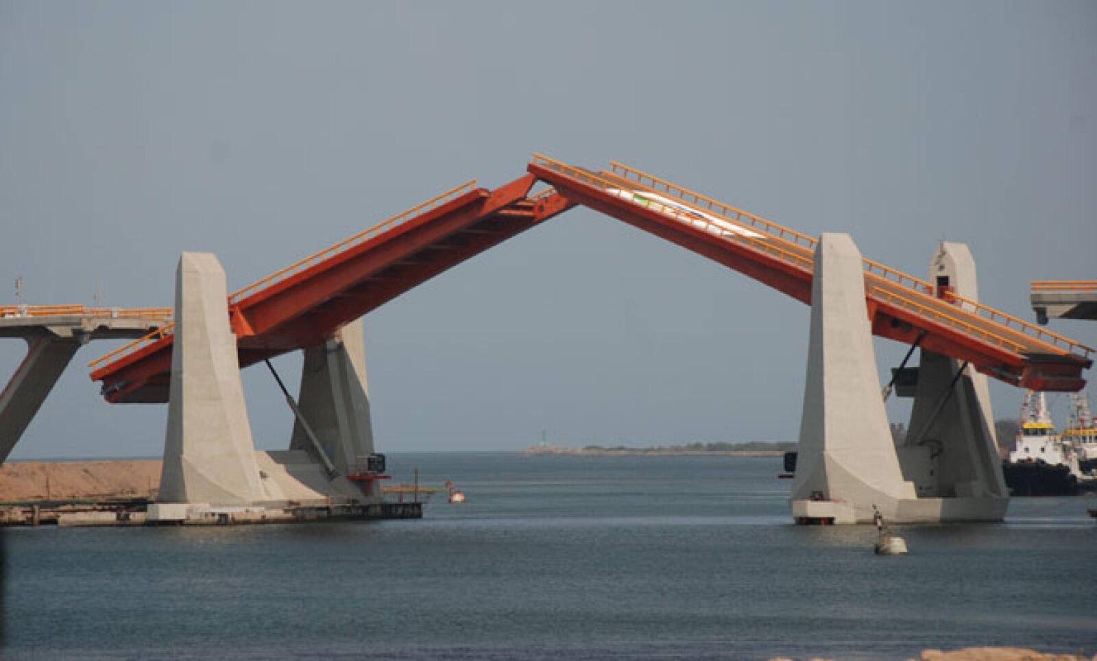 """Con sus 2,500 metros de longitud y 16 metros de anchura, las """"alas"""" del puente se abren en seis minutos para permitir el paso de barcos de la marina mercante que navega por las aguas del Río Balsas."""