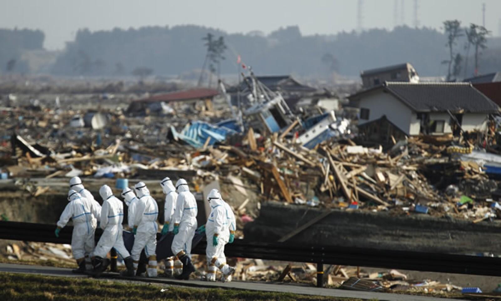 Policías japoneses cargan un cuerpo sin vida, después del terremoto y tsunami que azotó el país oriental el 11 de marzo.