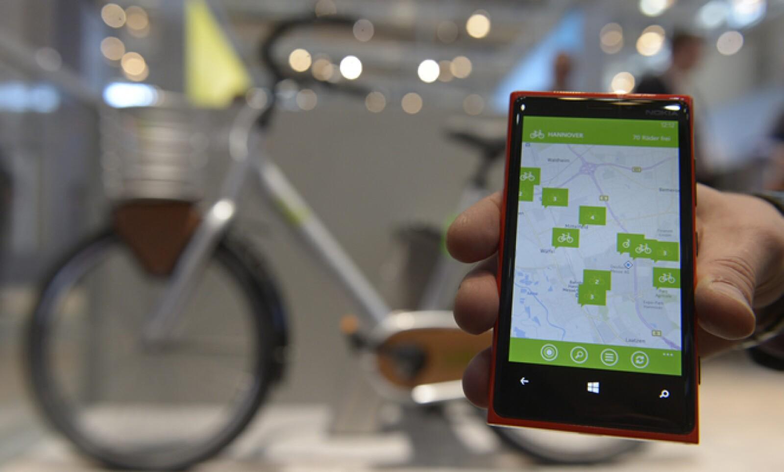 Un empleado posa con un teléfono inteligente para demostrar un sistema de intercambio de bicicletas llamado Contoso Bikes.