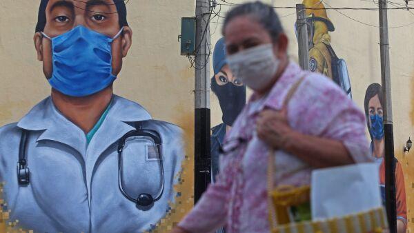 Una mujer con cubrebocas camina por el centro de Zapopan, al fondo se observa el mural Los héroes de la pandemia por Covid-19, una obra que conmemora y reconoce al personal que participa en esta contingencia.