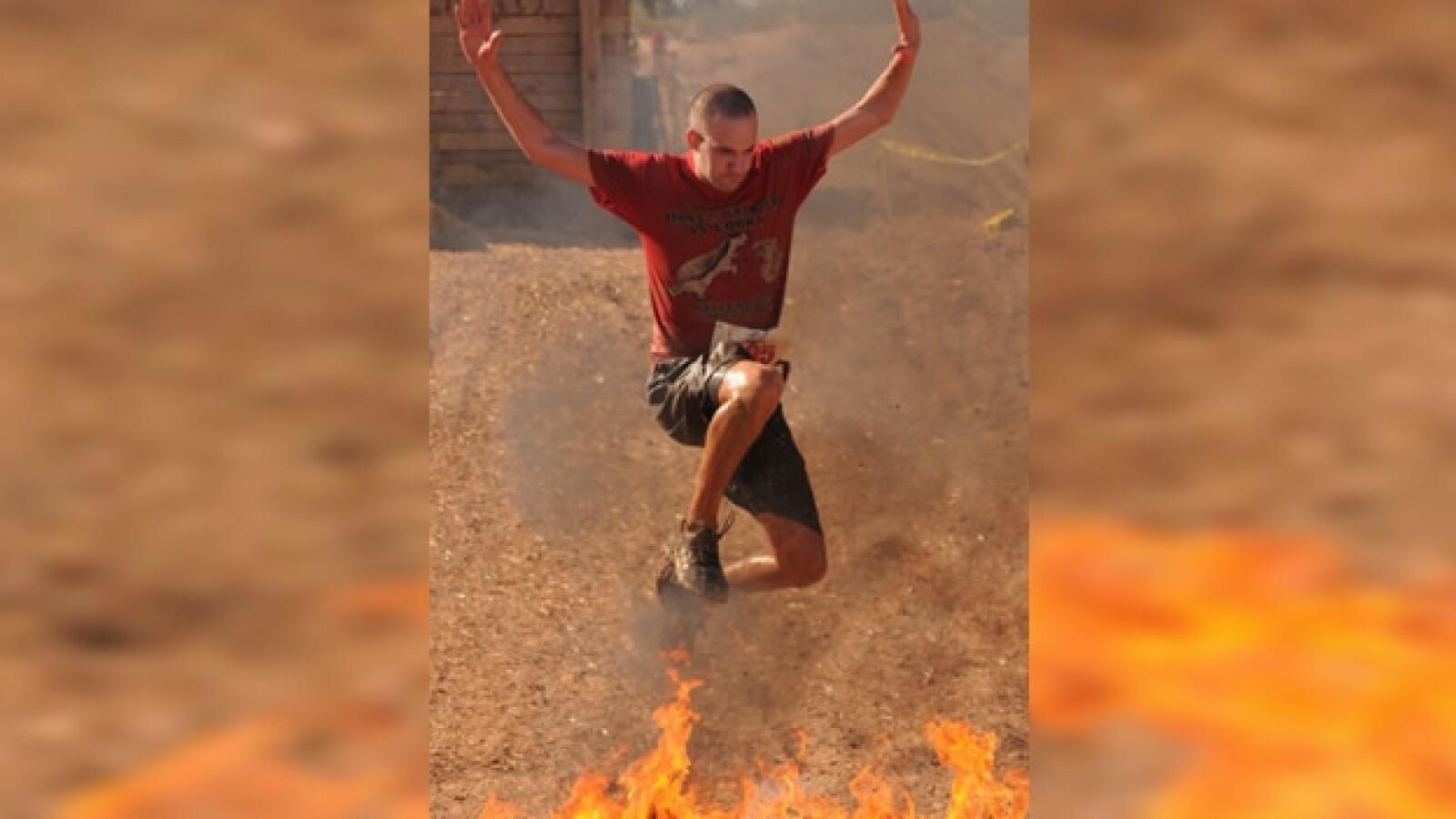 un chico salta sobre fuego