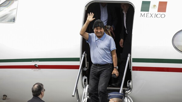 Bolivia's ousted President Evo Morales waves during his arrival to take asylum in Mexico, in Mexico City