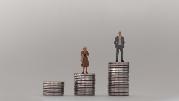 A miniature man and a miniature woman standing on a stack of coins of different heights. The concept of a gender pay gap.