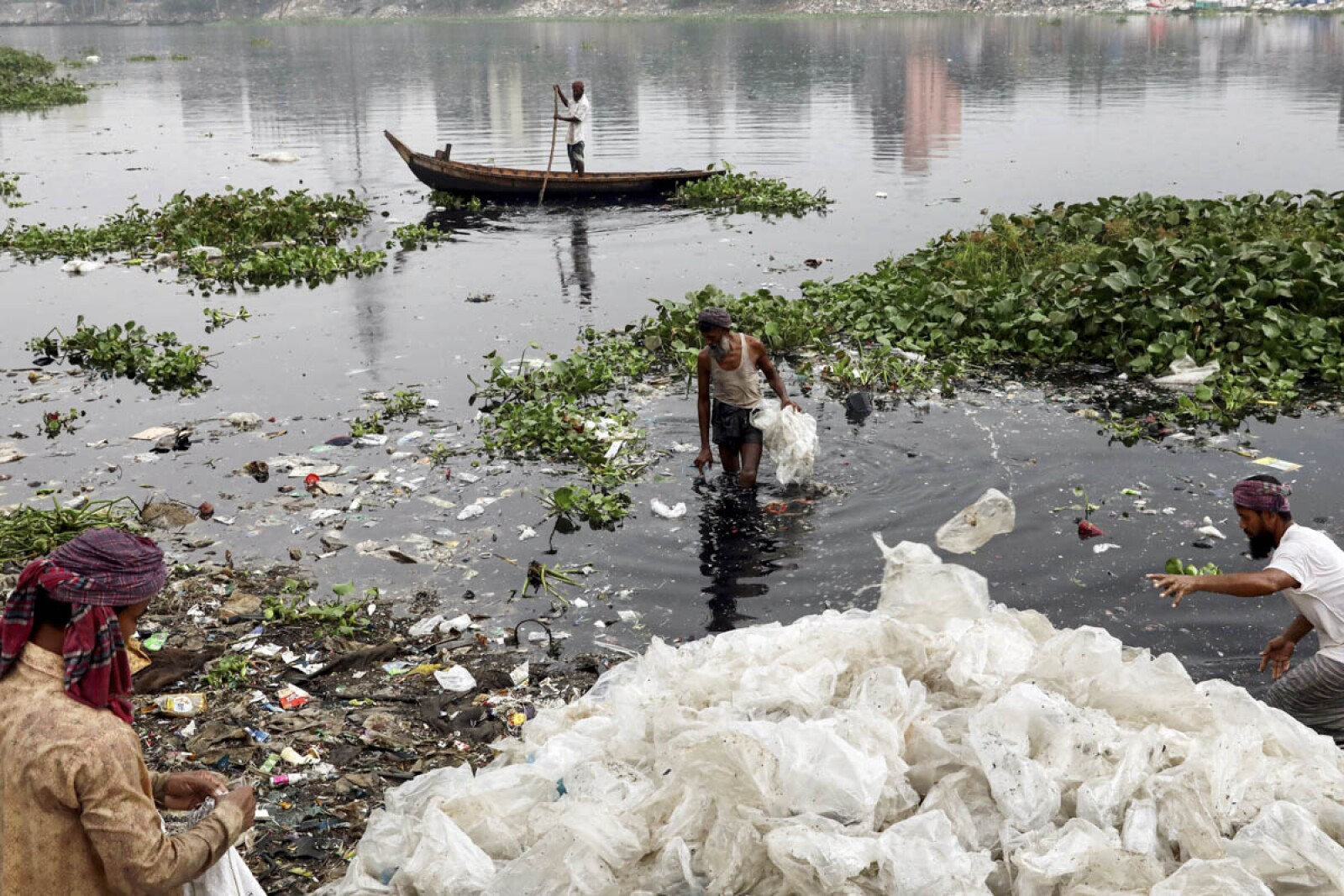 Men wash plastic waste in the waters of the Buriganga river before recycling it, in Dhaka