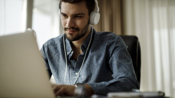 Young man using laptop and listening to music