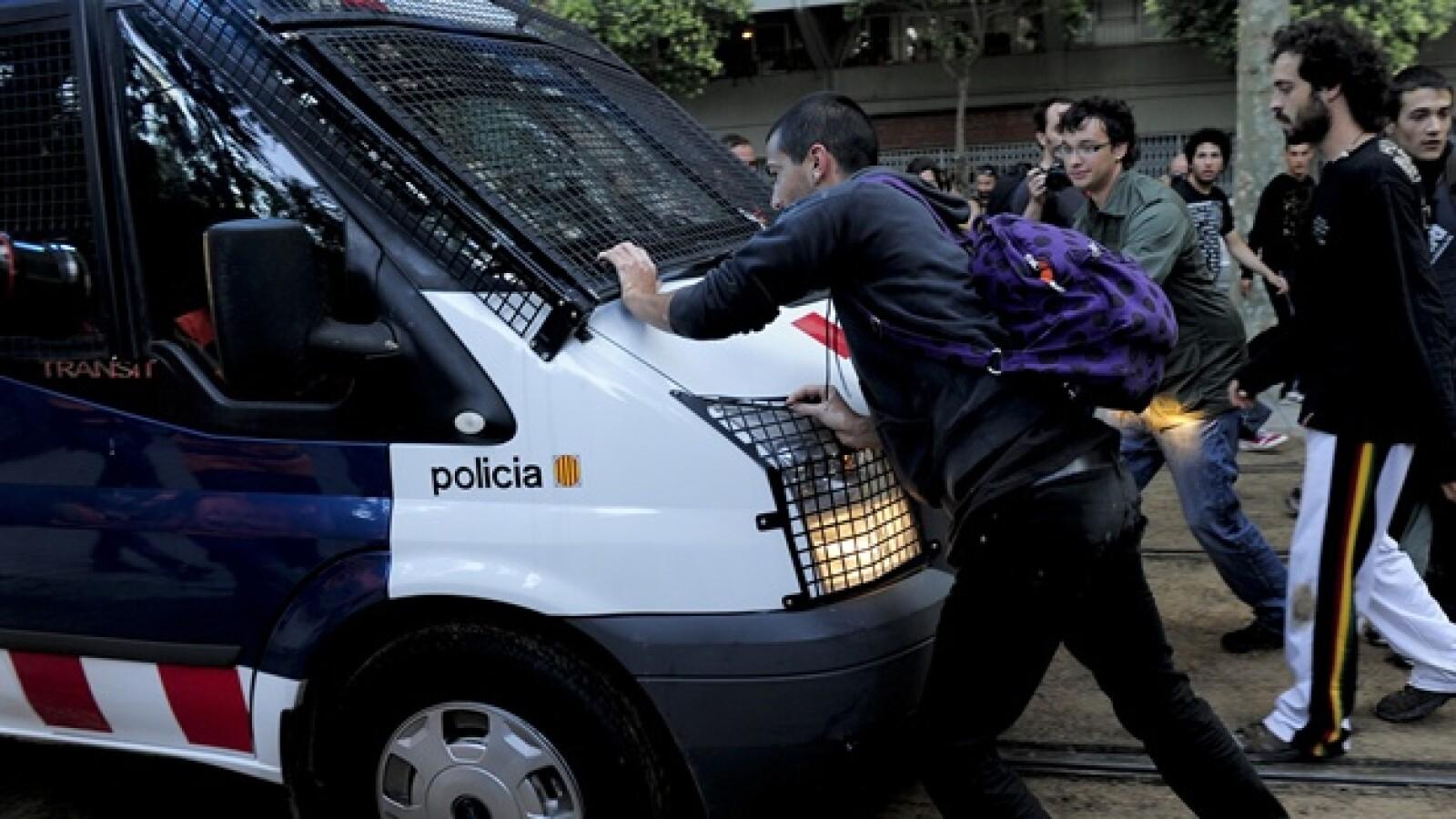 manifestantes evitan el paso de una patrulla