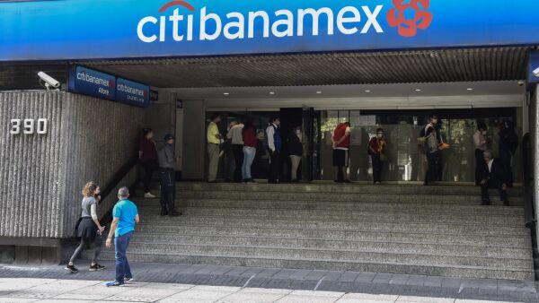 Persona esperan en una fila de una sucursal bancaria.