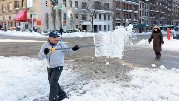 Un hombre retira la nieve acumulada en una de las calles de Nueva York, a fin de evitar accidentes entre las personas que transitan o los vehículos que se desplazan