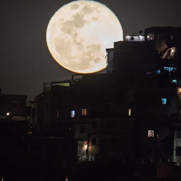 La esplendorosa luna se asoma a una favela en Brasil