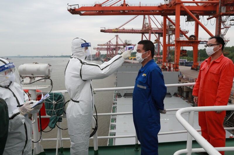Staff member takes body temperature measurement of a crew worker at a port in Wuhan