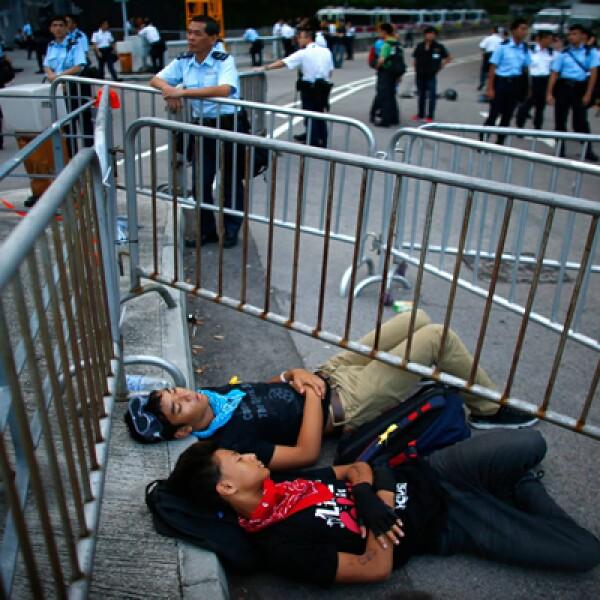 Los manifestantes se mantienen atrás de las vayas y ayudan a la gente a pasarlas cuando lo necesitan.