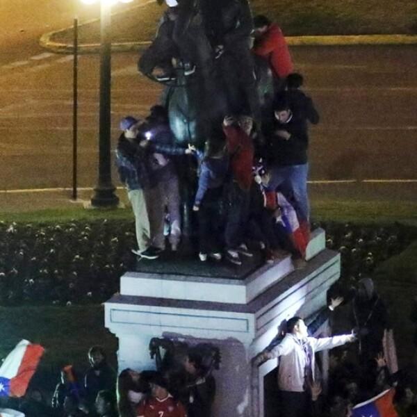 Otros chilenos aprovecharon el júbilo para subirse a monumentos como el de Manuel Badequano en Santiago