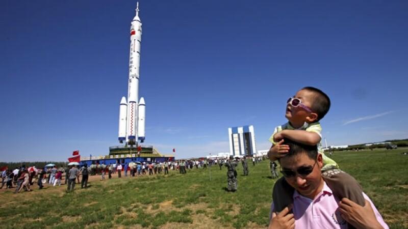 chinos posan junto a la nave Shenzhou IX