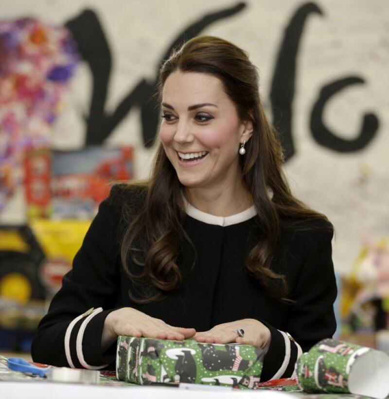 La duquesa de Cambridge hizo un peculiar gesto de sorpresa al recibir &#39golpeadas&#39 instrucciones de un miembro del staff del centro infantil que visitó cuando ayudaba a envolver regalos para niños.
