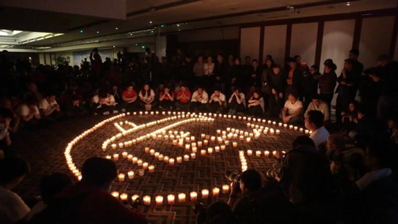 Las familias de los pasajeros desaparecidos en el vuelo 370 de Malaysia Airlines llevan a cabo una vigilia con velas este martes en Beijing, China