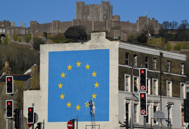 A large mural depicting the EU flag being chipped away, and attributed to the British artist Banksy is seen with Dover Castle behind, at the Port of Dover