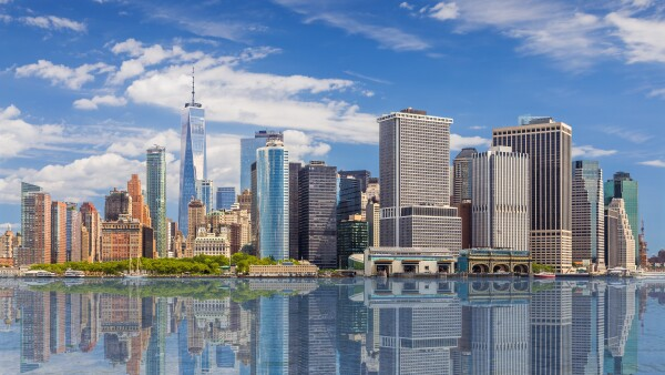 New York City Skyline with Manhattan Financial District and World Trade Center Reflected in Water of New York Harbor, NY, USA.
