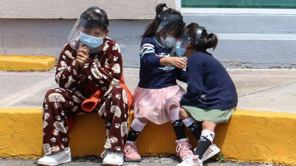 Tres niños esperan sentados sobre la banqueta a sus familiares en el área de urgencias del Hospital Ajusco Medio.