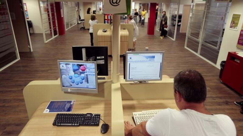 un hombre mira a su computadora en una agencia de empleo