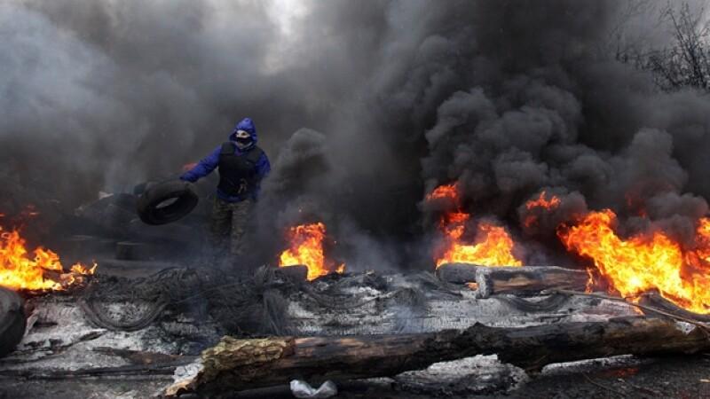un manifestante pro-ruso quema varias llantas mientras se prepara a combatir a las fuerzas especiales policiacas de Ucrania en la ciudad de Slaviansk, al este del país europeo