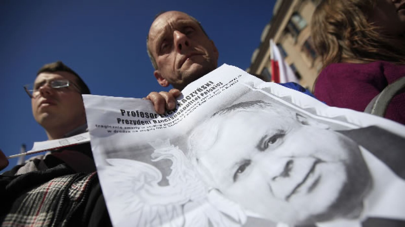Un hombre sostiene un poster
