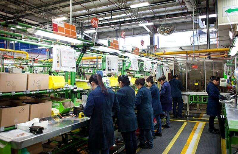 Vista de trabajadoras con los cuadernos de intrucciones del proceso, en la parte superior de su cabeza. Planta Schneider Electric