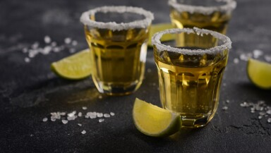 Gold tequila with lime and salt rim on dark stone or concrete background.