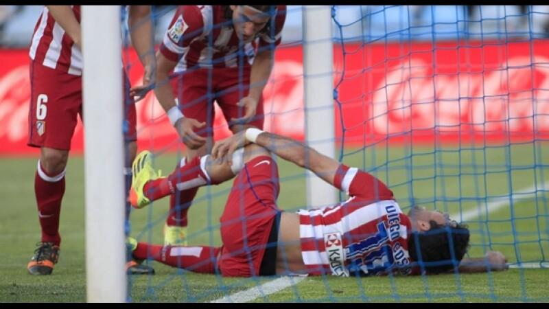 El delantero del Atlético de Madrid Diego Costa se duele de un golpe en su pierna tras anotar