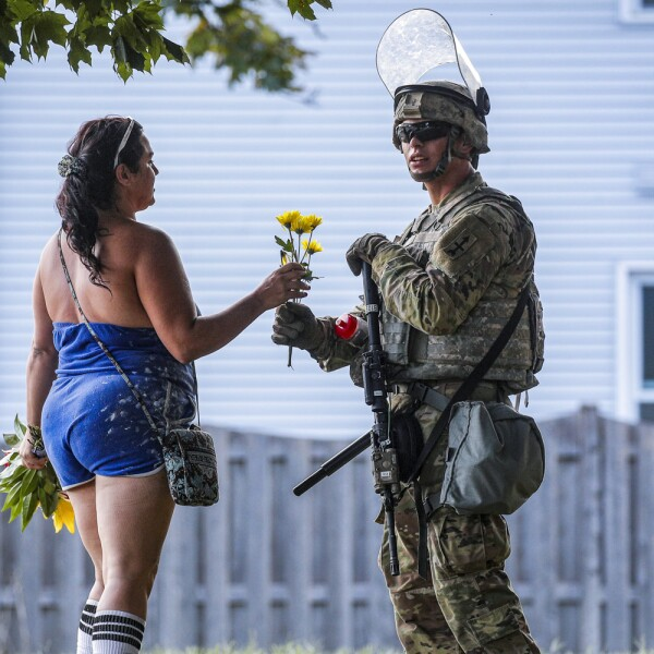 A woman hands flowers to a member of the Wisconsin National Guard standing by as people gather for a vigil, following the police shooting of Jacob Blake, a Black man, in Kenosha, Wisconsin