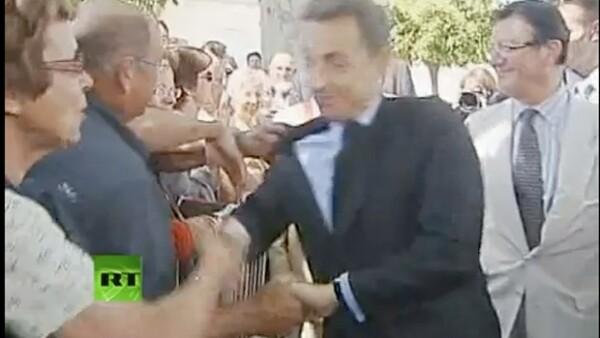 Un hombre tomó por el hombro al Presidente de Francia, mientras éste saludaba a la gente que se encontraba en el poblado de Brax, al sur de Francia.