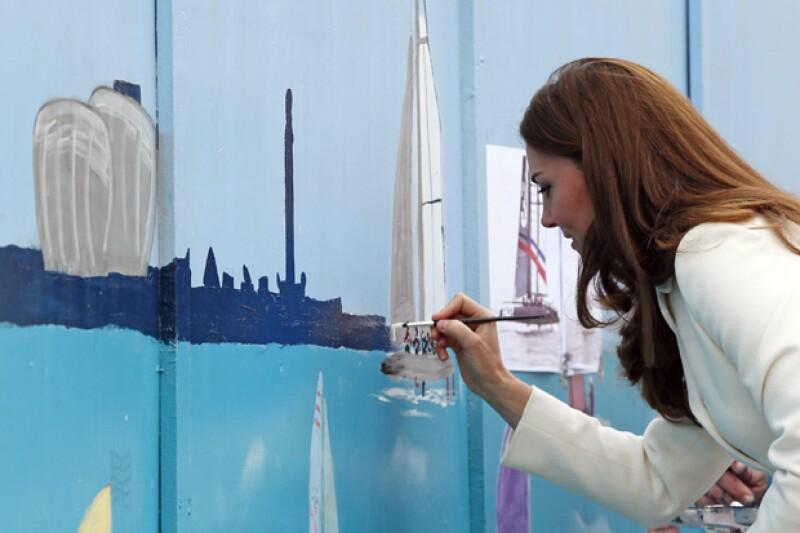Kate colaboró agregando algunos detalles a la pintura mural alusiva a la carrera de barcos que habrá en la localidad.