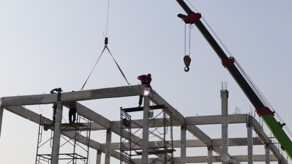 precast concrete beam installed at construction site by mobile crane