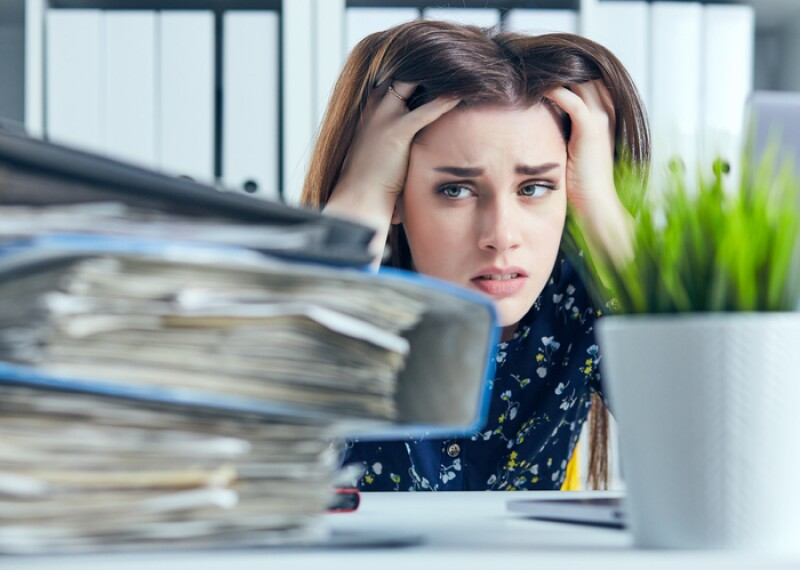 Tired and exhausted woman looks at the mountain of documents propping up her head with her hands